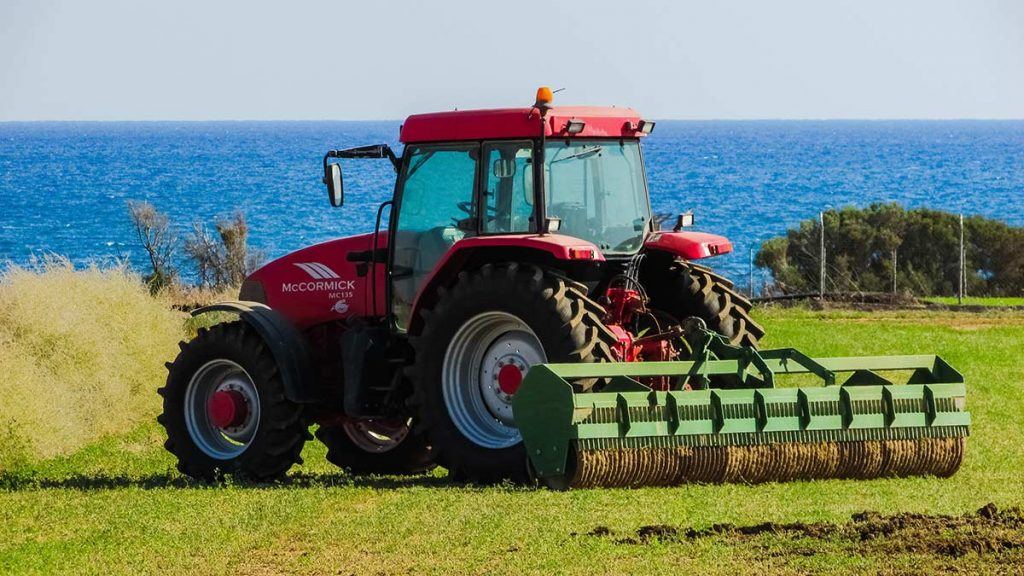 tractor in a coastal field with a roller attached